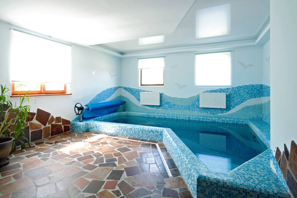 Small indoor pool with blue tile patterns and stone work for a small inside  pool deck