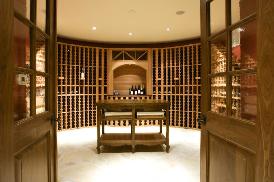 Large round wine cellar with tasting tasting table. Walls are in brick and wine cabinets made of wood.