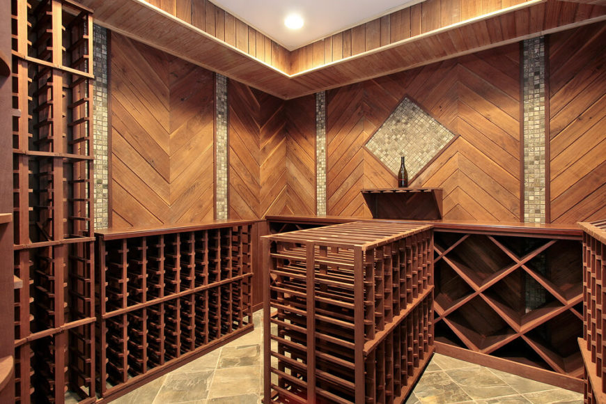 Wine cellar with waist-high wooden cabinets and wood paneling walls with tile inlay. Wine storing island is in the center of the room. I'd consider adding a flat top to the island to create a tasting area.