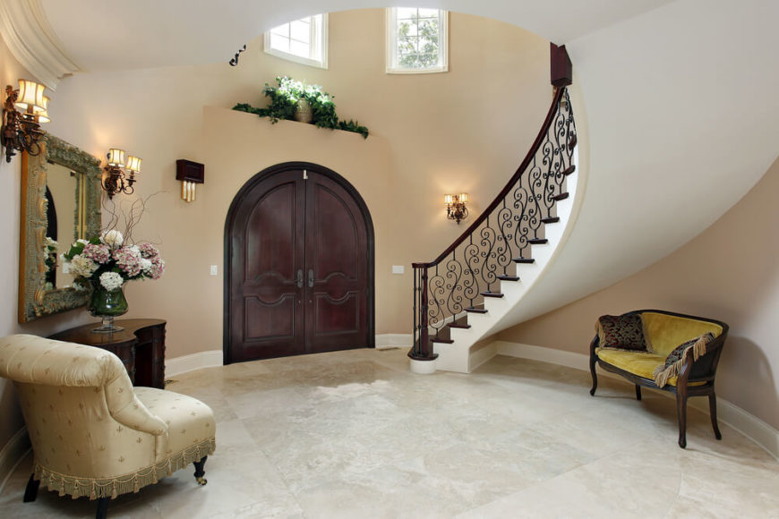 Circular entry way to luxury home. Small windows above the arched wooden door. Arched staircase with iron and wood railing descends to the front door. Small sitting area on the side opposite the stairs.