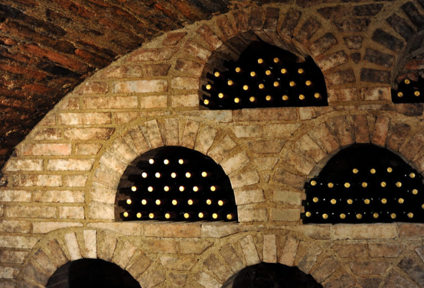 Close-up of a brick wall with built-in wine storage cubicles.