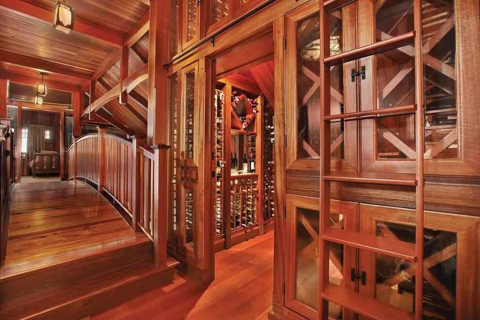 Incredible woodwork is the highlight of this wine storage room which includes a ladder for reaching wines. Wooden bridge provides access to the closed-off wine storing room.