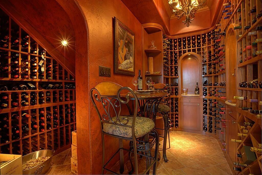 Richly designed wine cellar room with chandelier, floor-to-ceiling wine cabinets and small tasting table for two people.