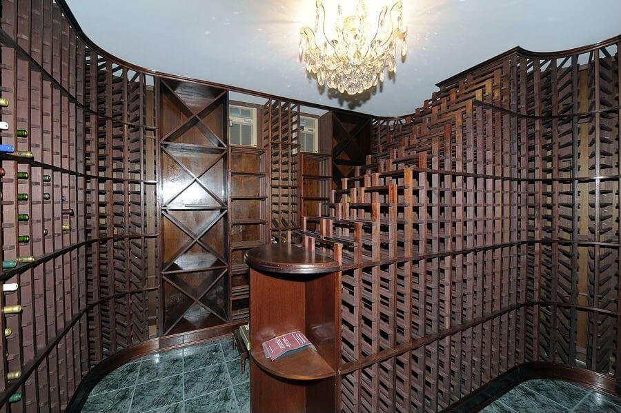 Wine cellar capable of storing thousands of bottles of wine in dark wood cabinets and green tile floor.