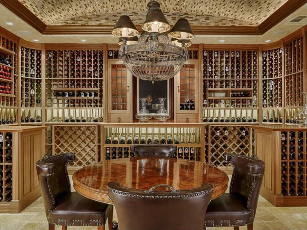 Wine cellar design with extensive custom cabinets for thousands of bottles of wine. The room includes a round table that accommodates 4 people for tasting wines.