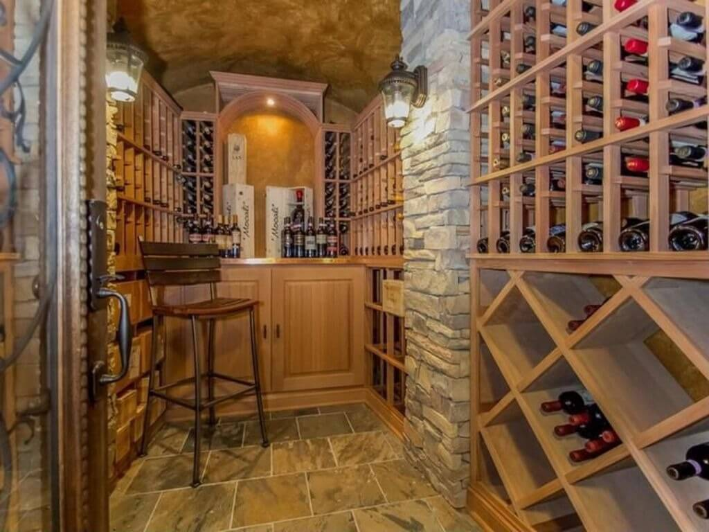 Cozy wine storage room designed in stone and wood with small sitting stool and counter for tasting.
