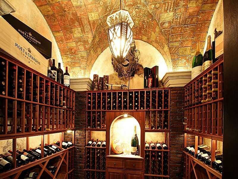 Small wine cellar with intricately designed ceiling. Cabinets include display storage sections for featuring select wines.