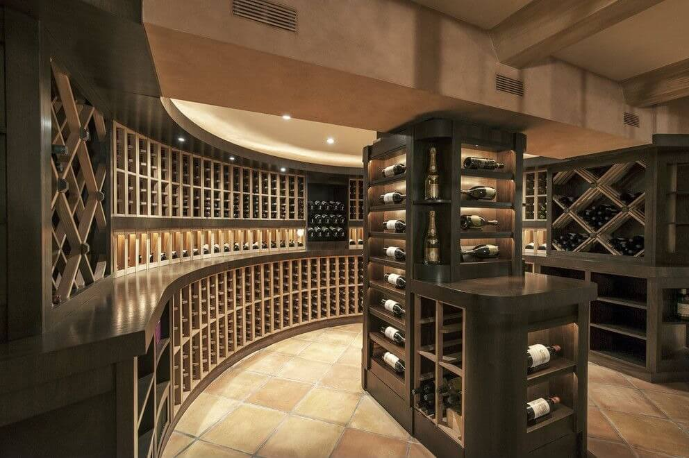 Large semi-circular designed wine cellar with extensive custom wood cabinets. Floor-to-ceiling wine cabinet forms an island in the center of the room with a display case for featuring wines.