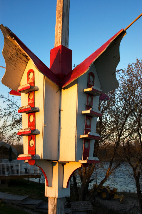 Massive Asian bird house design with red roof attached to a tall wooden pole.