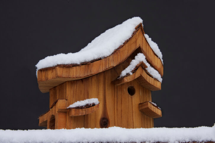 Asymmetrical bird house design made of wood. Small wooden awnings add a decorative touch to this bird house.