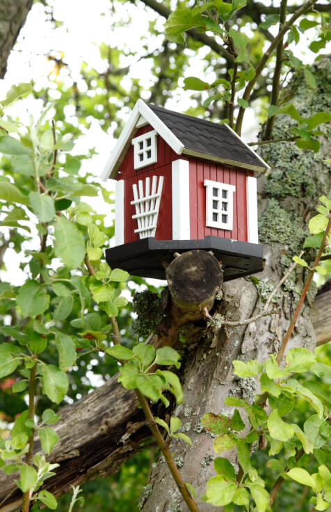 Scandinavian home style bird house in red and white color scheme placed on a branch in a tree.