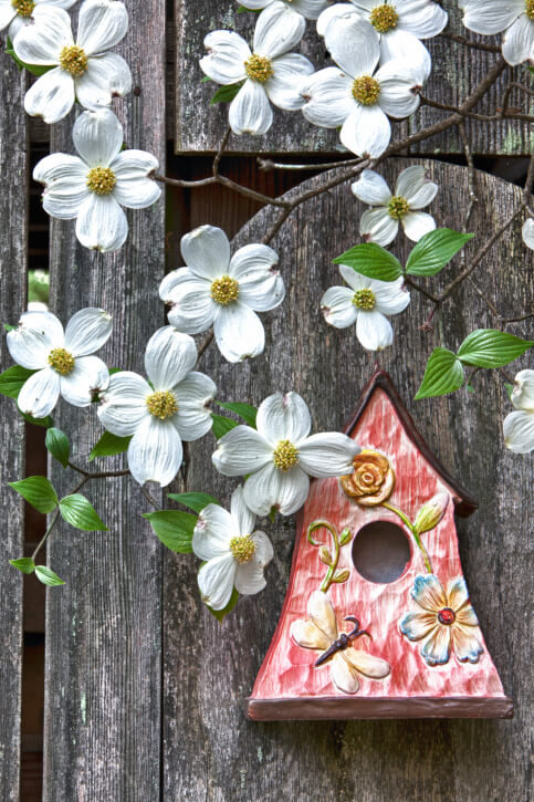 Red bird house with butterflies and flowers painted on it attached to a fence surrounded by flowers.