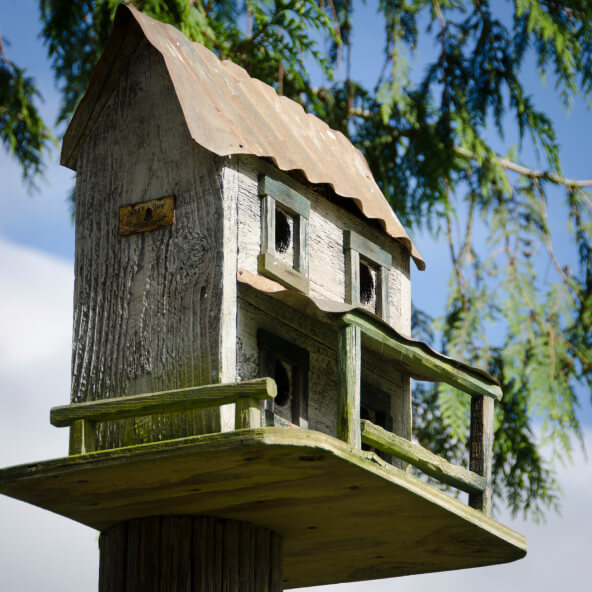 Bird house modeled after a farm house with veranda and tin roof.