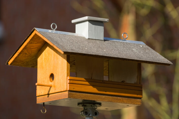 Brown-painted bird house with a real shingle for the roof. Hook loops attached to the roof so it can hang.