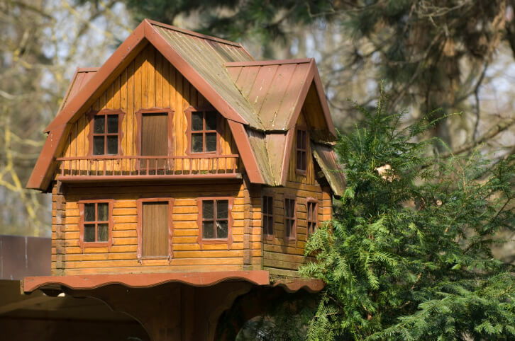 Large decorative log home bird house on a pole. It's a 2-story home with small upper level veranda.