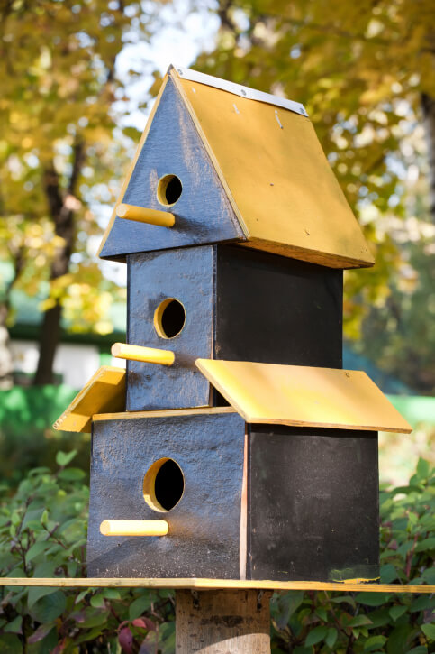 Simple three story bird house design with perch rods extending beneath the access holes.