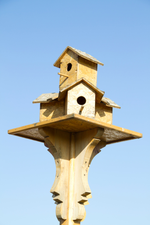 Three bird houses form the base for a second bird house perched on top.