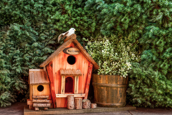 Custom bird house design with a wing painted in soft red. Roof is a series of small pieces of wood. Small logs in front of the house as a decorative bird house feature.