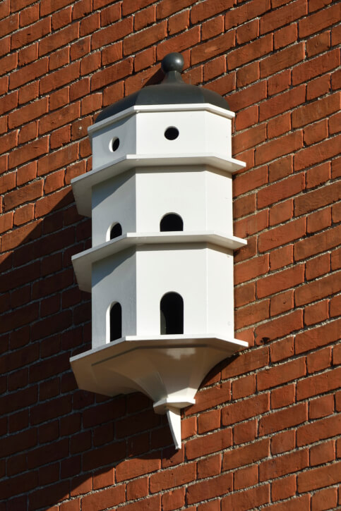 Three story white bird house attached to the side of a brick wall. Here's a great way to dress up a large windowless exterior wall.