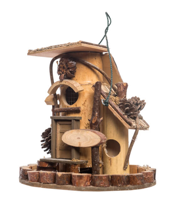 Elaborate bird house made with hollowed out tree branches dressed up with pine cones, small branches sitting on a wood base with a small log fence.