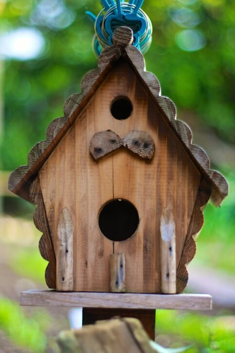 Simple wooden bird house with log siding and roof.