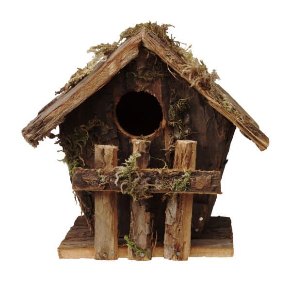 Rustic wooden bird house with wood fence in front.
