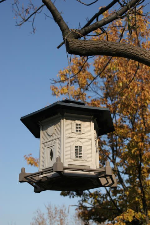 Picture of an well-crafted hexagon two story bird house replicating a home with front door, windows and wrap-around porch.