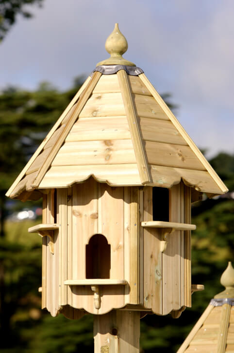 Natural wood 6-sided hexagon bird house with perch shelves underneath the bird access doors.