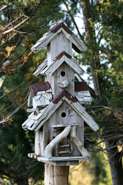 Rustic three-story drift wood bird house perched on a wooden post.