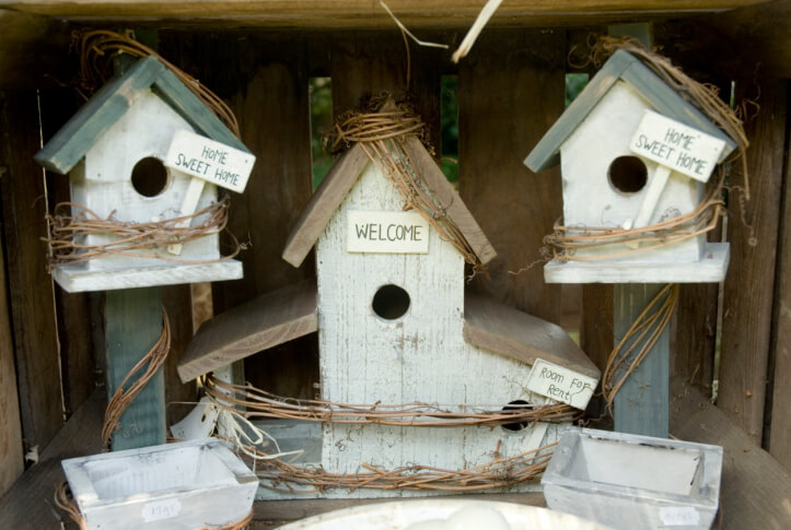 Series of 3 wooden bird houses in a display with mini bird baths.