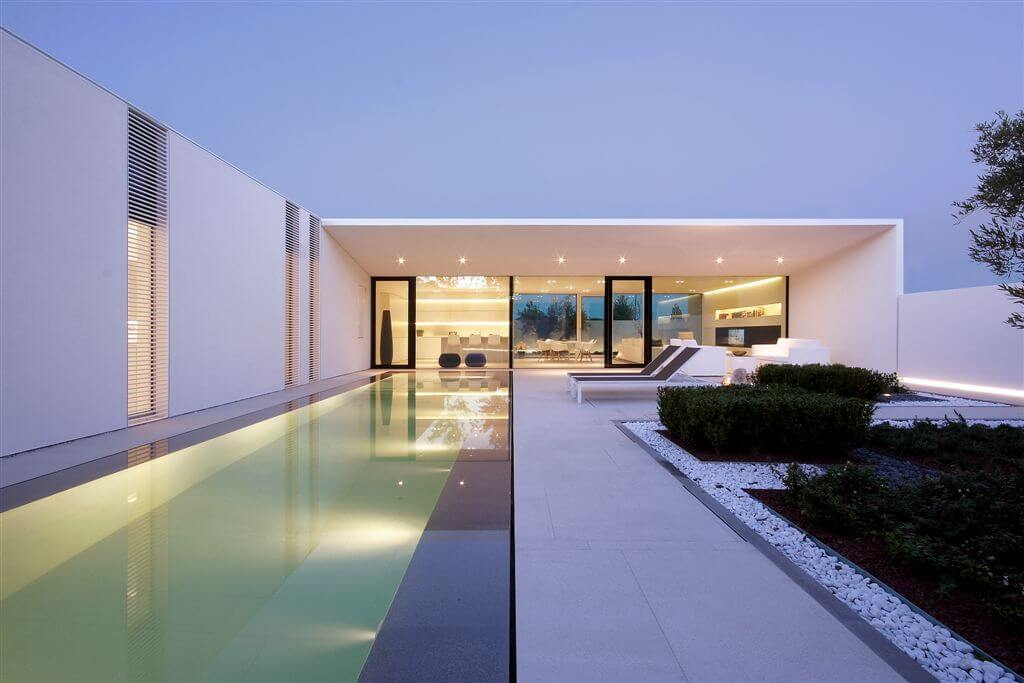 Straight-on view of home from poolside, highlighting precise right angles and lengthy pool.