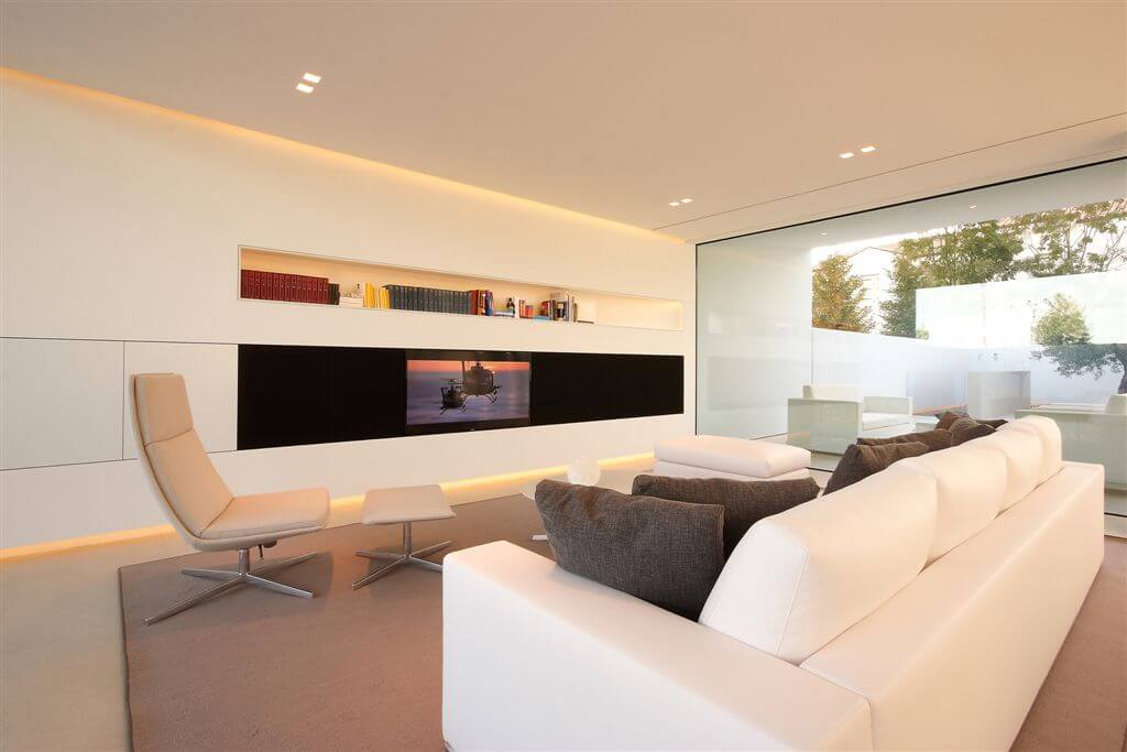 Front living room with light tan flooring and leather chair, all-white walls and black strip camouflaging television.