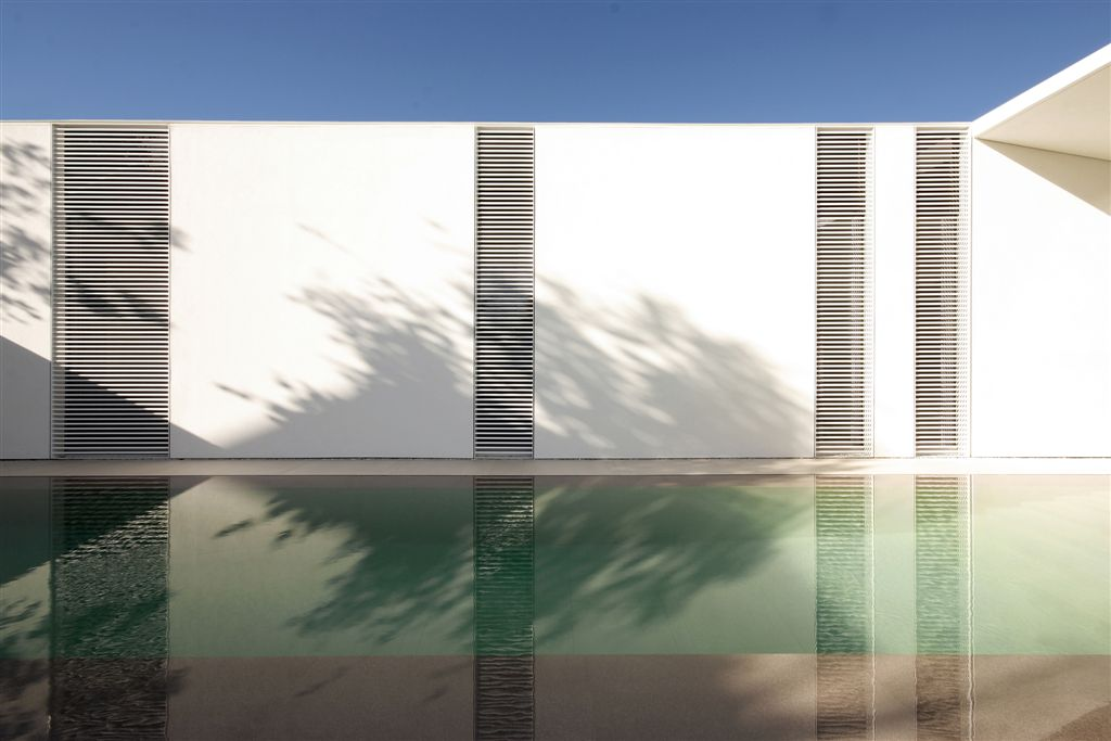 Floor to ceiling windows with sun-blocking slats reflected in pool.