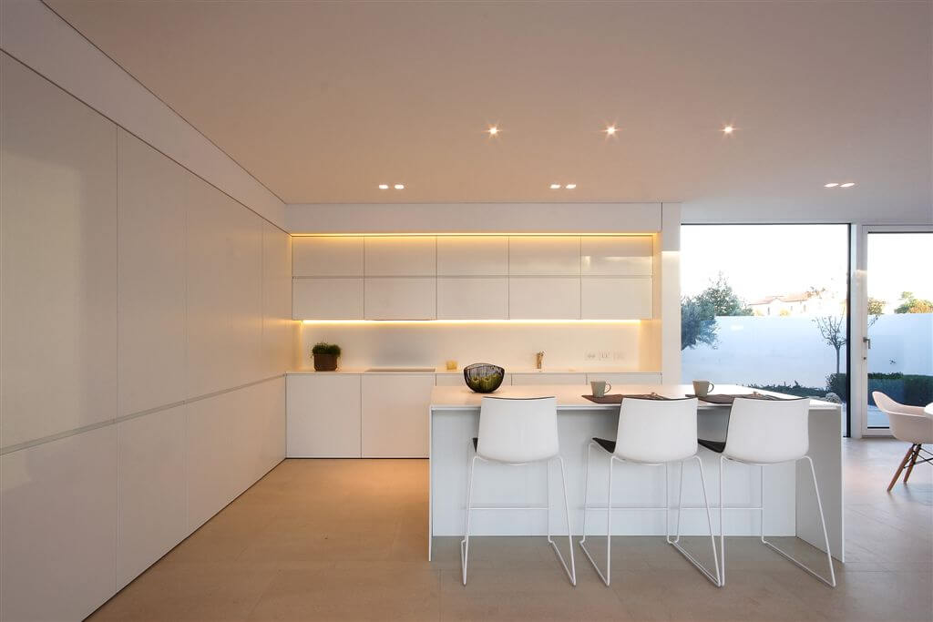 Kitchen area features hidden lighting around cupboards, all-white minimal surfaces, and bar-style seating at island.