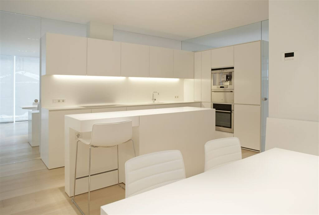 Here's a shot of the ultra modern kitchen, all-white with light hardwood flooring.
