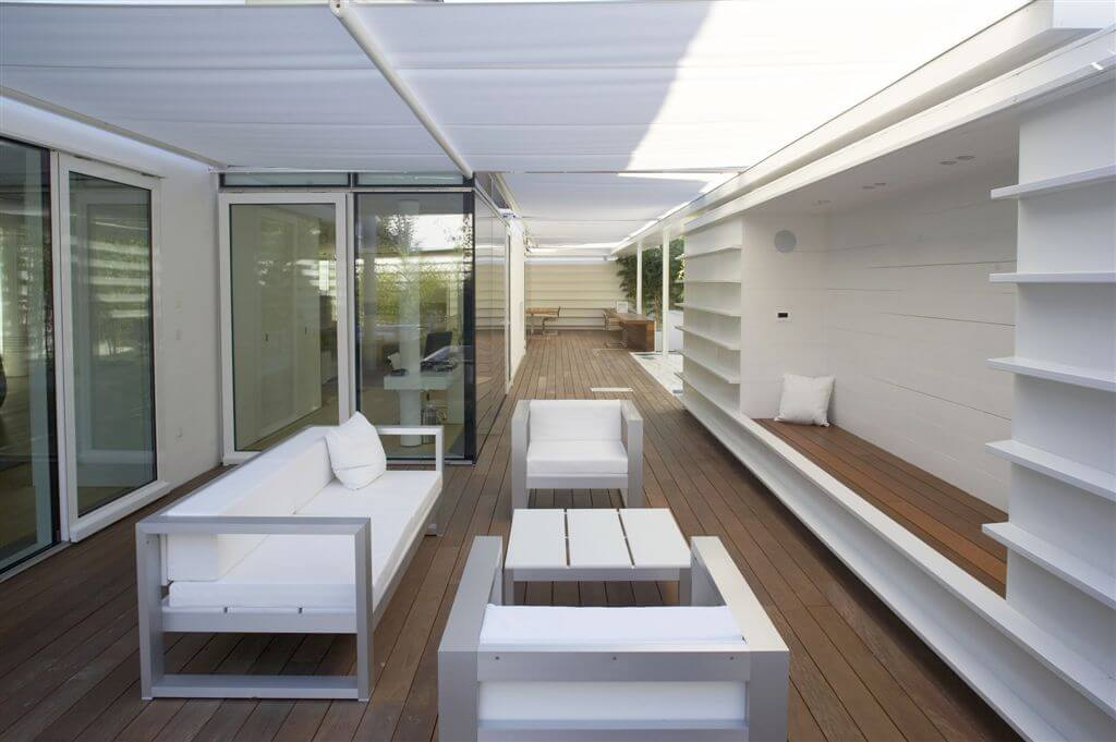 Opposite view of deck area, highlighting the white and metal couch and chairs, shelve-style seating and large glass doors.