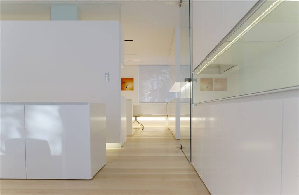 Hallway featuring large expanses of glass set against smooth white surfaces, with corner office area in background.