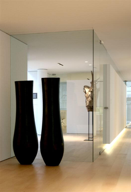 Second hallway angle showcasing glass walls, embedded lighting, and large art pieces.