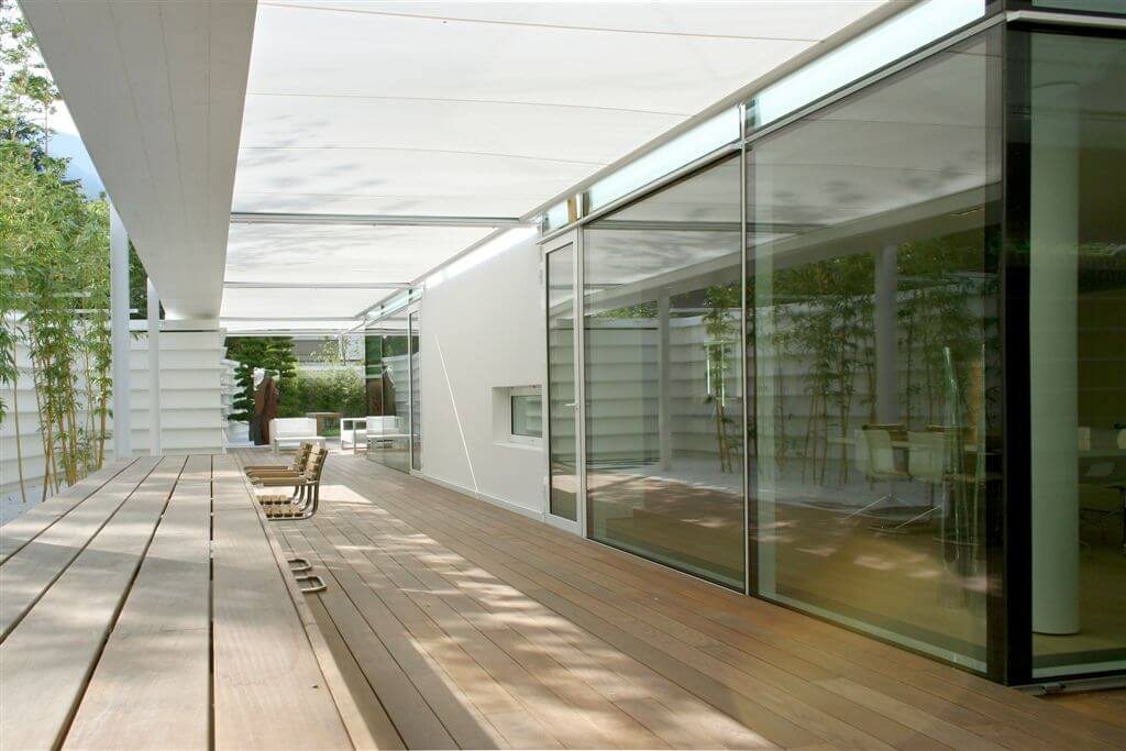 Long view of deck with canopy, glass walls and see-through fireplace.