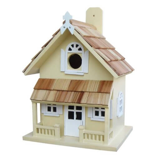 Victorian house bird house with front porch, wood shingle roof, white door and windows.