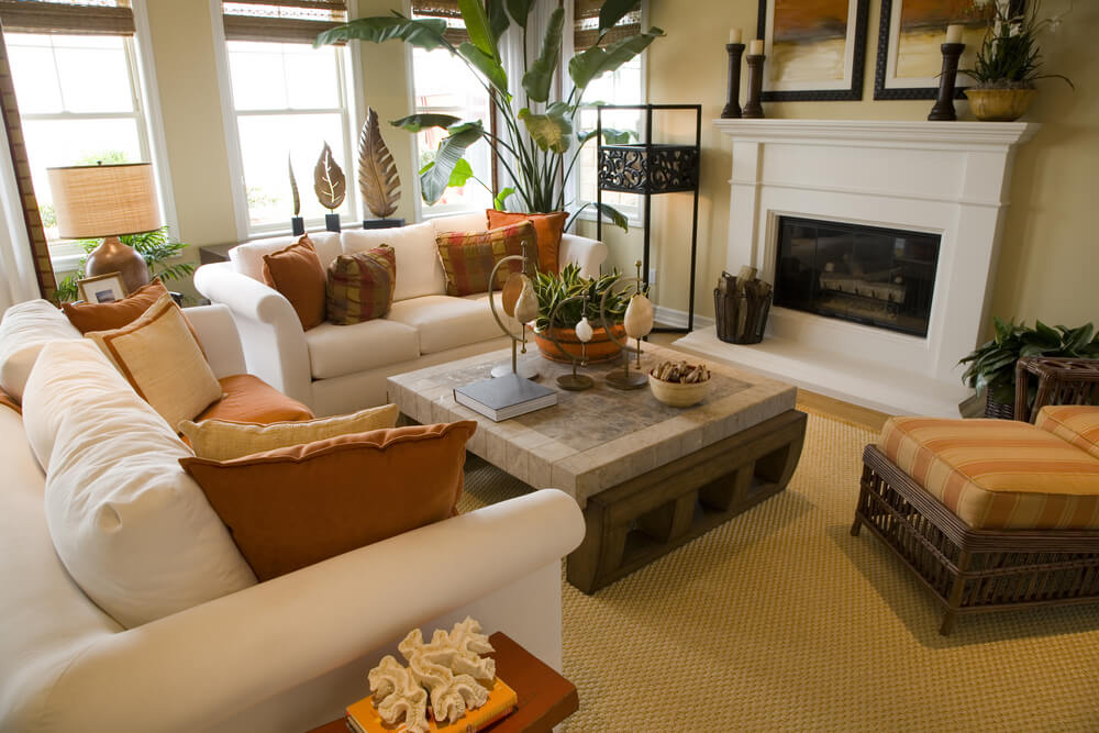 bright and colorful living room design with off white sofas decorated with orange and brown