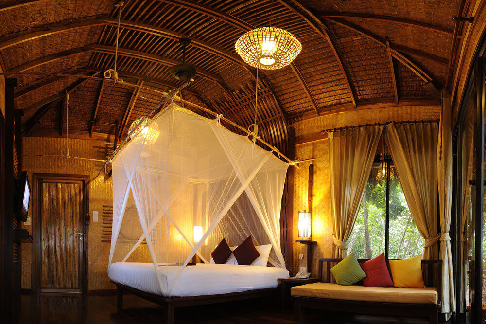 Birds nest style bed in tropical arched room.