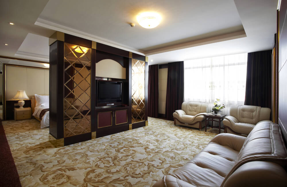 Wide hotel room divided by entertainment center with mirrored gold surfaces.