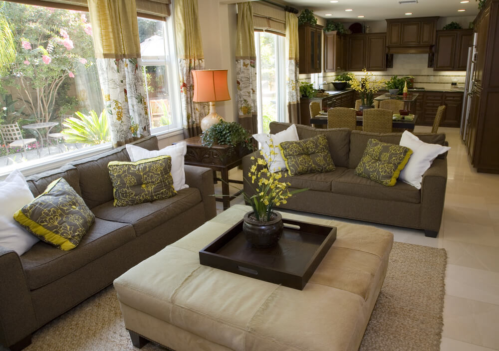 Two Brown Sofas With Yellow And Brown Patterned Pillows With White Pillows  Surrounding A Large Beige