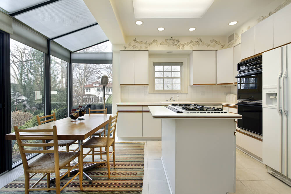 Sunlit Open Kitchen Design Featuring All White Cupboards Tile Floor And Island