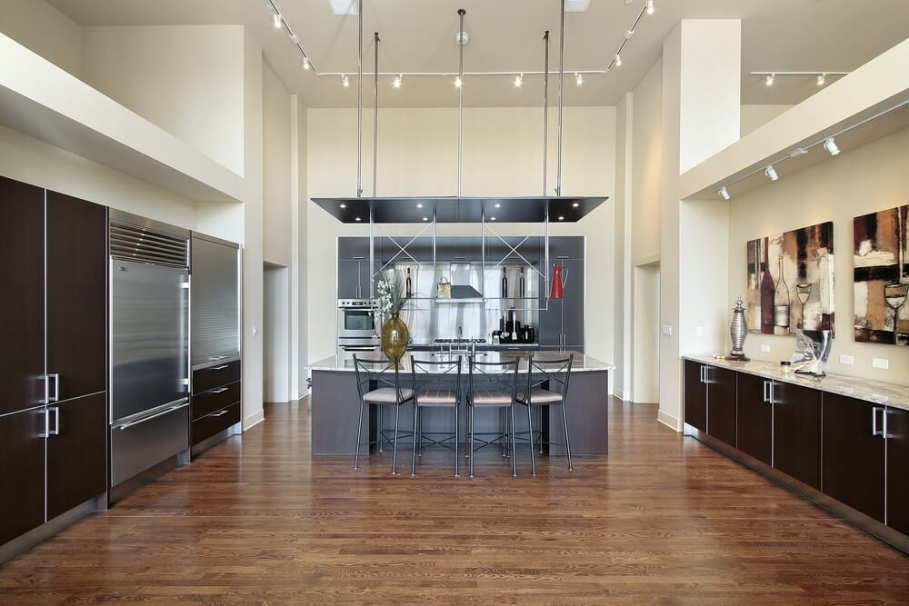 Modernist kitchen highlighted by extensive metal work over natural hardwood floor and dark minimal wooden cabinet doors.