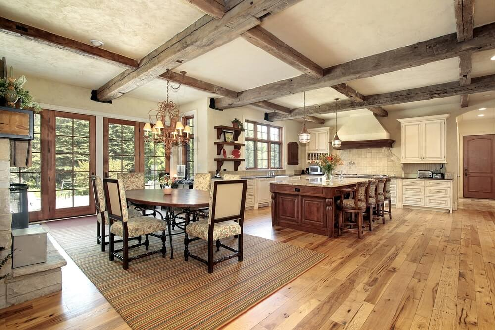 The natural exposed wooden beams in this spacious kitchen compliment the wooden tones on the doors, island, and flooring.