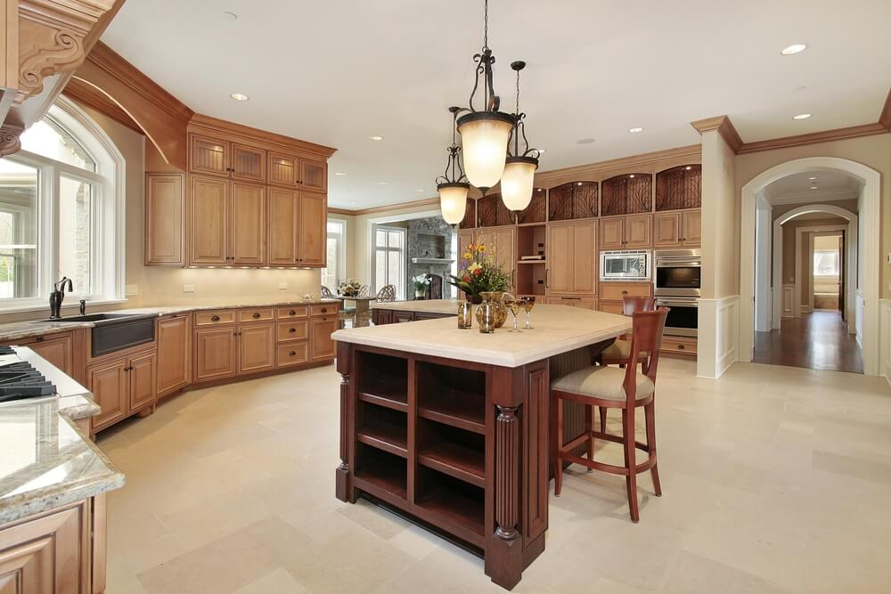 This kitchen features unique open-view doors with internal lighting on top of standard light wood tone cabinets and a light sand colored floor.