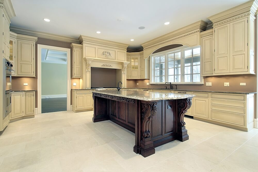 With cabinetry similar to the prior kitchen, this example features a dark stained wooden island with a secondary sink and granite countertop.