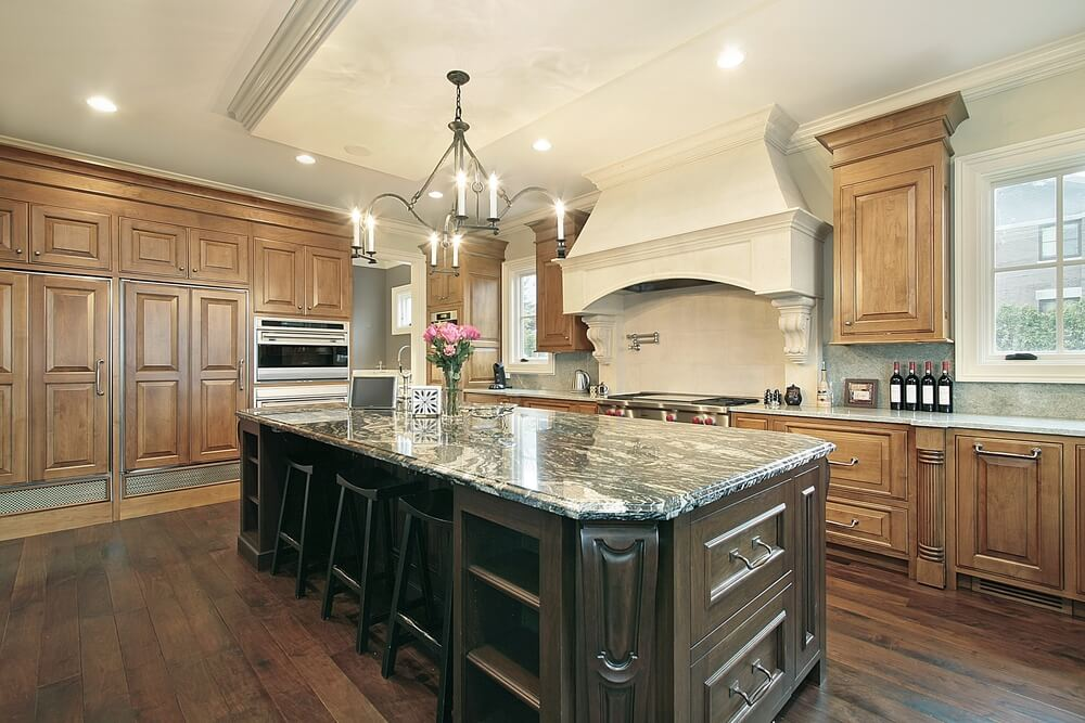 Dark wooden island with marble top stands out in this kitchen featuring lighter wooden cabinets and medium colored hardwood floor.